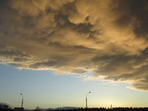 Yellow gray storm clouds. Cumulonimbus dramatic sky wave formation over the city. Weather after the thunderstorm, light. Blue sky and sunset sun shining glow stock photos