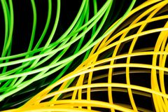 Yellow and green ABS plastic for 3D printer. Black background royalty free stock photos