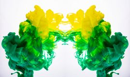 Yellow and green acrylic paint, abstract color clouds underwater. Macro shot of acrylic pigment blending in liquid. Two royalty free stock photos