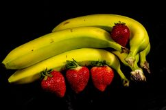 The yellow and green banana`s and  four red fresh sweet strawberrys. Fruits of four different banana cultivars Royalty Free Stock Photos