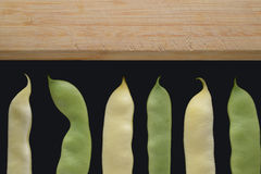 Yellow and green beans on a cutting board. Stock Image