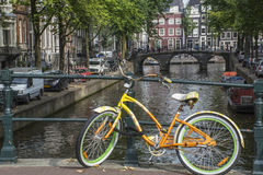 Yellow and green bike with old bridge and buildings Stock Images