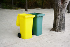 Yellow, Green bins public trash on sand. Royalty Free Stock Image