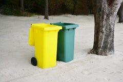 Yellow, Green bins public trash on sand. Royalty Free Stock Image