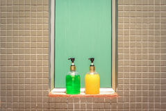 Yellow and green bottles of liquid soap and shampoo in bathroom Stock Photography