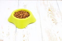 Free Yellow-green Bowl With Dry Cat Food On A White Wooden Floor Royalty Free Stock Image - 103041276