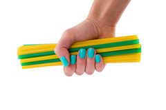 Yellow and green cocktail stick in a female hand. Bunch of yellow and green tubules for a cocktail in a female hand Royalty Free Stock Images
