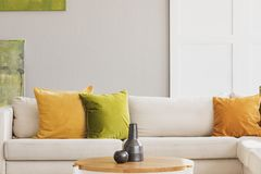 Yellow and green cushion on white settee in simple living room interior with wooden table. Real photo. Yellow and green cushion on white settee in simple living stock photography
