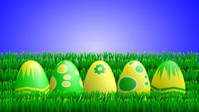 Yellow Green Easter Eggs in Grass. Easter illustration of a row of yellow and green painted Easter eggs lying in the grass Royalty Free Stock Photo