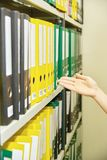 Yellow and green file folders in archive and human hand Royalty Free Stock Photos