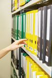 Yellow and green file folders in archive and human hand Stock Photo