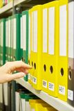 Yellow and green file folders in archive and human hand Royalty Free Stock Photography