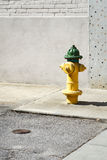 Yellow And Green Fire Hydrant In A City. An American bright yellow & green fire hydrant on a city street corner sidewalk on a sunny day. The space on the left Stock Images