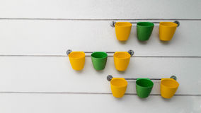 Yellow and green flowerpots hang on the rail. Stock Photo
