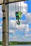 Yellow-green hook of a construction crane on a rope on a background of clouds Royalty Free Stock Photos