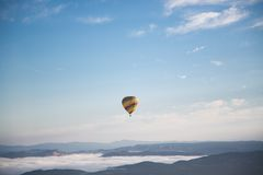 Yellow and Green Hot Air Balloon Floating on Mid Air Under Blue and White Sunny Cloud Sky Royalty Free Stock Photo