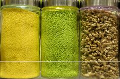 Yellow and Green Jimmies. Jars of yellow and green jimmies, and walnuts above frozen yogurt counter Royalty Free Stock Image