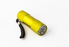 Yellow-green led aluminum flashlight on a white background Royalty Free Stock Photo