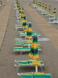 Yellow and green loungers and umbrellas  along an Italian beach. Yellow and green beach chairs and umbrellas arranged along an Italian beach Royalty Free Stock Photo
