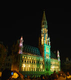 Grand Place in Brussels. Yellow and green night illumination of medieval tower on Grand Place in Brussels, Belgium Royalty Free Stock Photography