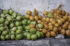 Yellow, Green, Orange coconuts at Badung traditional market, Bali - Indonesia. Stock Photo