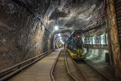 Yellow and green passenger train in a mine Stock Images