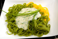 Yellow and green pasta with sauce Royalty Free Stock Images