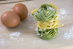 Yellow and green pasta with two eggs on wooden table Royalty Free Stock Photography