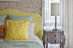 Yellow and green and pattern pillows on classic style bed Royalty Free Stock Image