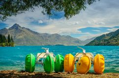 Yellow and green pedalo on lake stock image