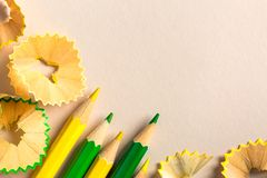 Yellow and green pencils  and shavings. On paper background Stock Images