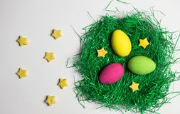 Yellow, green and pink Easter egg in nest of artificial green grass with yellow decorative stars all over white background. royalty free stock images