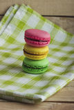 Yellow, green and pink macarons on the plaid napkin. Yellow, green and pink macarons on the green plaid napkin, soft focus background Royalty Free Stock Photo