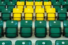 Yellow and green plastic seats in the stands of the sports complex. Auditorium for sports fans. Seats for spectators of a football stock images