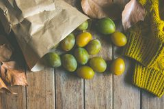 Yellow Green Plums in Brown Craft Paper Bag Scattered on Plank Wood Table Dry Autumn Leaves Knitted Sweater Fall Cozy Atmosphere Royalty Free Stock Images