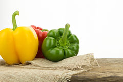 Yellow, green and red bell peppers on wooden surface Stock Image