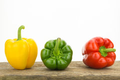 Yellow, green and red bell peppers on wooden surface Stock Photo