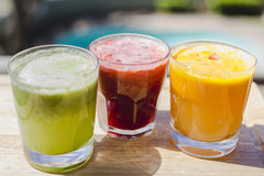 Yellow, green and red fruit and vegetable juices in tumbler glas Stock Images