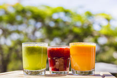Yellow, green and red fruit and vegetable juices in tumbler glas Stock Photo