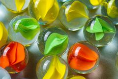 Yellow, green and red glass marbles on a table