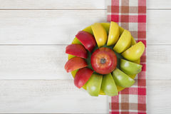 Yellow, green and red quartered apples laid out around the whole apple on a saucer Royalty Free Stock Photography