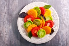 Yellow, green, red tomatoes. Sliced on plate Royalty Free Stock Images