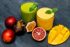 Yellow and  green smoothies with tropical fruits Royalty Free Stock Photography