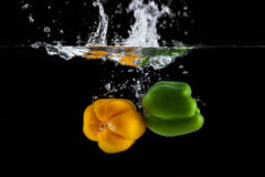 Yellow and green sweet pepper splash into a black color. Of water Stock Images
