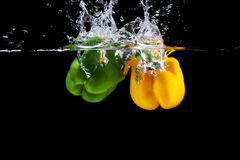 Yellow and green sweet pepper splash into a black color. Of water Royalty Free Stock Images