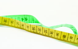 Yellow and green tape measure on white background Royalty Free Stock Photo