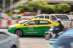Yellow green taxi in scenery motion blur on the street Bangkok Stock Image