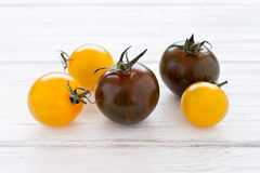 Yellow and green tomatoes. On a white wooden board Stock Photography