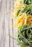 Yellow and green uncooked pasta tagliatelle Royalty Free Stock Photos