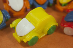 Yellow green and white plastic bettle. On a orange background with another plastic bettles stock photography